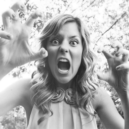 An image of Grace Helbig holding her hands up like claws.